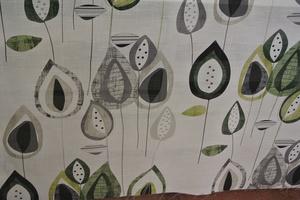 Lannister på ljus botten med blad i gröna,svarta och grå toner