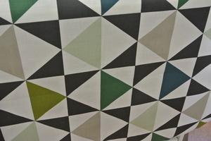 ljus botten med trianglar i svart och gröna nyanser