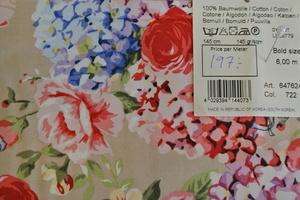 blommigt bomullstyg i rosa toner på beige botten